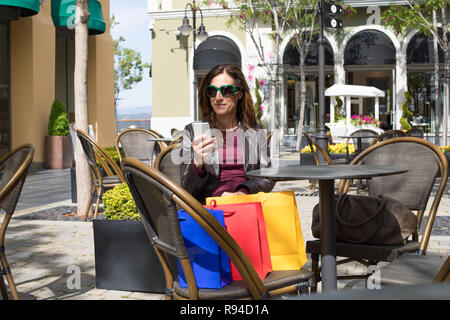 brown hair woman with red shirt, leather blazer and sunglasses sitting at urban cafe terrace outdoors, at street, watching smart mobile phone with sho - Stock Image