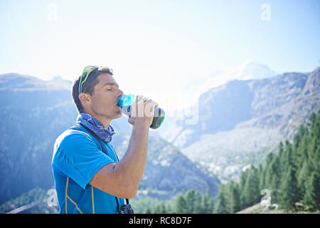 Hiker drinking from water bottle, Mont Cervin, Matterhorn, Valais, Switzerland - Stock Image
