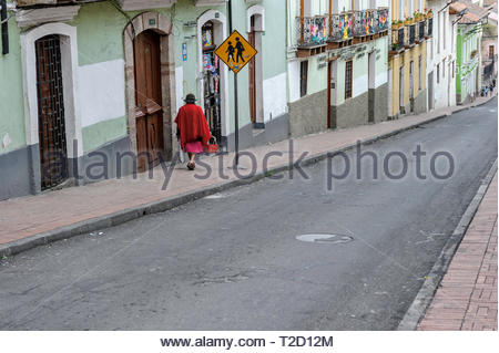Indigenous woman walking in the  Quito Old Town (Centro Histórico) district.  UNESCO-listed historic center. - Stock Image
