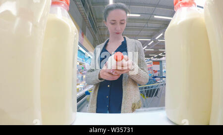Woman buying fresh milk at supermarket - Stock Image