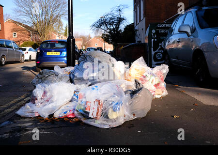 Large clear plastic bags full of domestic refuse are left lying on the pavement of a street awaiting collection by the local authority - Stock Image