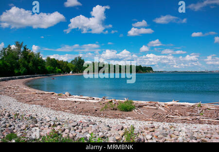 Beautiful sunny day with people on beach in blue water under blue sky and white clouds in Rouge National  Urban Park, Toronto, Ontario, Canada - Stock Image