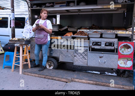 Candid photo of a woman food vendor under the elevated subway on Roosevelt Avenue in Jackson Heights, Queens, New York. - Stock Image