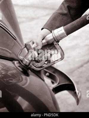 1940s MALE HAND PUMPING GASOLINE FUEL INTO CAR - m2926 HAR001 HARS OLD FASHIONED - Stock Image