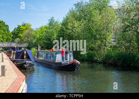 Narrowboat sailing on the Basingstoke Canal passing through Woking town centre by the Saturn Trail, Surrey, southeast England on a sunny day - Stock Image