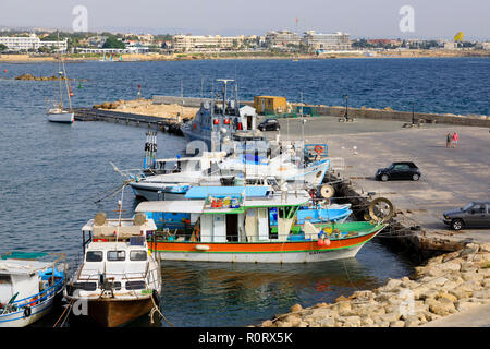 Paphos harbour, Cyprus October 2018. Local traditional fishing boats share the quay with the police coastguard boat. - Stock Image