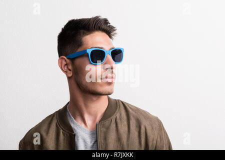 A confident young hispanic man with blue sunglasses in a studio. - Stock Image