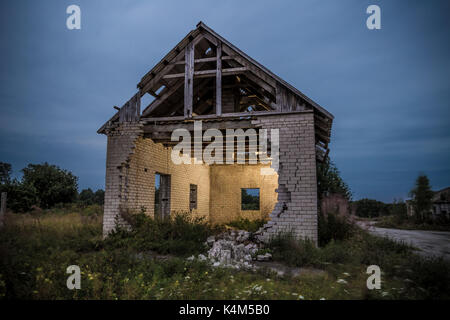 Decayed house with fallen wall and inside lit up by flash - Stock Image