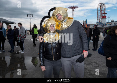 A couple wearing old fashioned diver's helmets pose for a photo prior to the annual Polar Bear Club New years Day swim in Coney Island, Brooklyn, NYC. - Stock Image