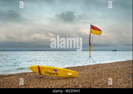 RNLI lifeguard yellow board and red and yellow safe are flag on a shingle beach. - Stock Image