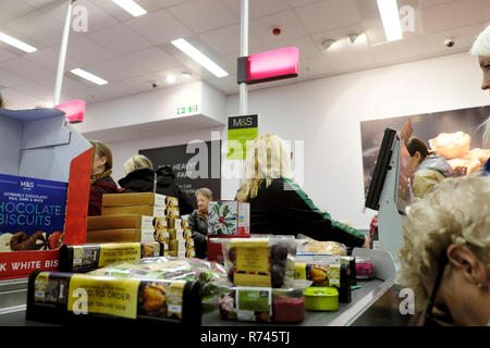 An older female worker working on the checkout counter in M&S Marks and Spencer food grocery store in Great Britain UK. KATHY DEWITT - Stock Image