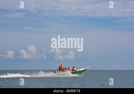Tourists in boat approaching Bako National Park - Stock Image