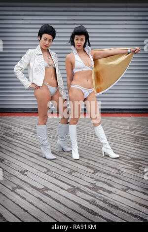 Posed portrait of two Chinese Elvis Presley impersonators in bikinis at the annual Polar Bear Club New Year's day swim in Coney Island, Brooklyn, NYC. - Stock Image