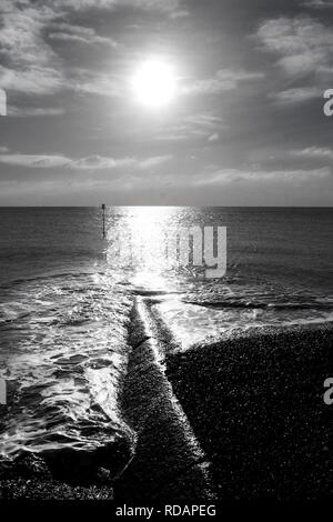 Black and white photograph of the low winter sun shining onto a flat calm sea, a long high light reflecting on the sea and across a long sea break hal - Stock Image