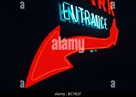 Neon entrance sign with red arrow - Stock Image