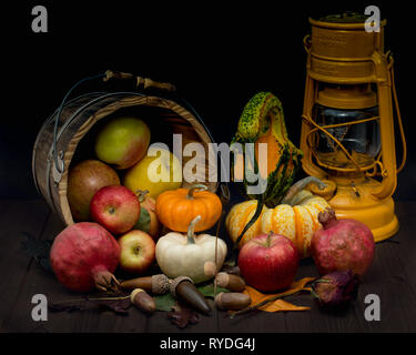 Abstract still life displaying  harvest symbols and a German gas lantern, against wooden background and decorated with colorful fall leaves - Stock Image