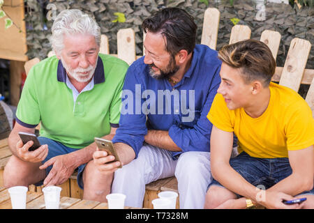 family generations men with grandfather father and son nephew from old to young stay together using cellular technology smartphone to connect to inter - Stock Image