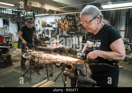 Caucasian female blacksmith grinding on a metal part in her studio.  Male blacksmith at work in the backround. - Stock Image