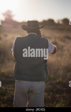 Rear view of man taking picture during safari vacation - Stock Image