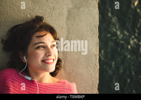Happy beautiful girl in pink sweater listening to music in white earphones lying in the wall next to the sea at sunset. - Stock Image
