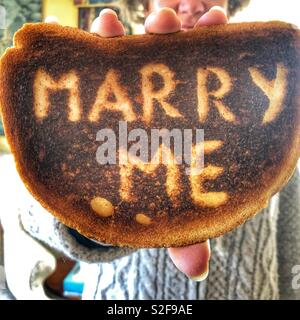 Creative love and romance concept.  Woman holding up a piece of burnt toast with the words Marry Me scraped on the surface. - Stock Image