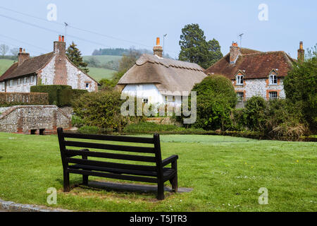 Empty bench on country village green by pond in South Downs National Park. Singleton, Chichester, West Sussex, England, UK, Britain - Stock Image