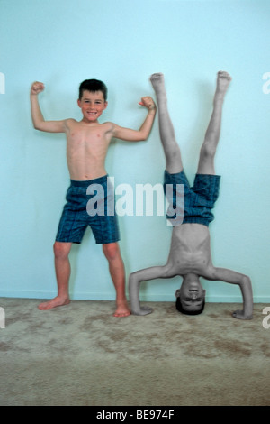 upright & upside down 11 year old twin boys posing against a wall - Stock Image