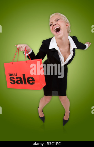 Beautiful blond woman with a red final sale shopping bag on a green isolated background - Stock Image