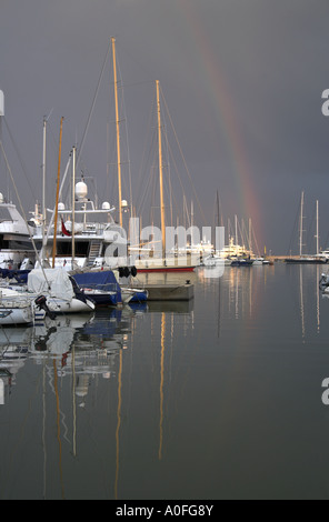 Rainbow and Sailing Yachts in Antibes Harbour, Cote d'Azure, South of France - Stock Image