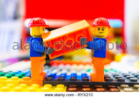 Poznan, Poland - March 14, 2019: Two Lego construction workers carrying together a orange brick. - Stock Image