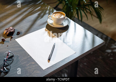 Close up of white coffee cup, oat cookies, glasses, blank sheet of paper and pen on dark wooden table with tropic plant on background. - Stock Image