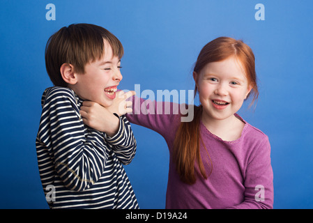 Girl 6 tickles boy 8 around neck on a plain blue background. Boy is laughing because he is ticklish - Stock Image