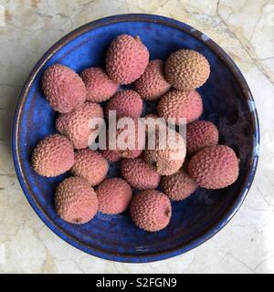 Lychees in a blue ceramic bowl on marble - Stock Image