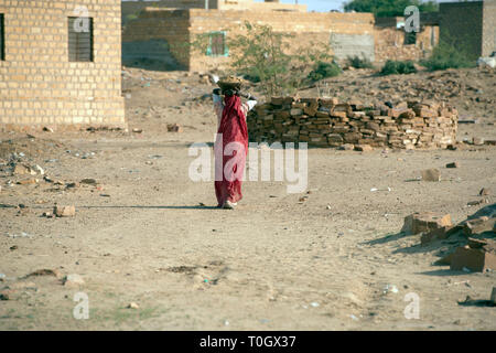 An Indian lady walks home carrying a pot on her head. Rajasthan, India. - Stock Image