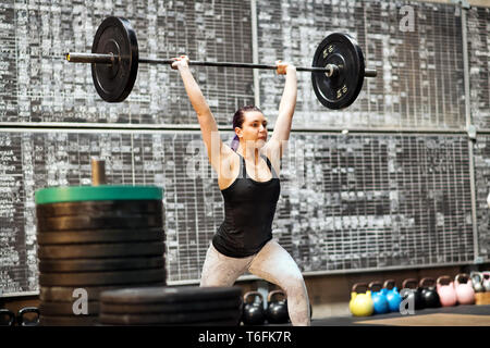 Young woman performing a clean and jerk exercise in a gym during training lifting the barbell above her head with extended arms after first moving it  - Stock Image