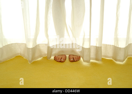 A naked women's legs and feet behind a sheer curtain. Yellow carpeting floor - Stock Image