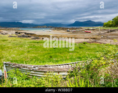 View across Sound of Sleat with boats in harbour and dilapidated rotting rowing boat, Ardvasar, Isle of Skye, Scottish Highlands, Scotland, UK - Stock Image