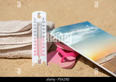 Bournemouth, UK. 26th June 2018. UK Weather, a heatwave in June. Sandy beach in Bournemouth with towels and flip flops and thermometer to check the temperature with the tourist information guide book. Credit: Thomas Faull / Alamy Live News - Stock Image