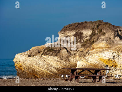 Large Rock and Picnic Area on Beach - Stock Image