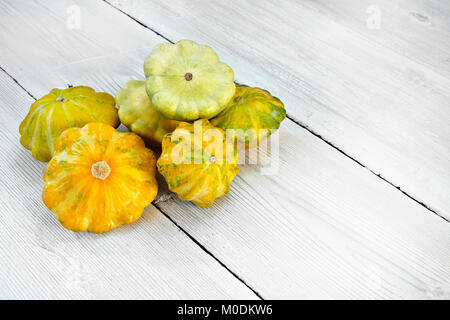 Five yellow and green bush pumpkins on white wood background. Garden,agriculture and farming concept. - Stock Image