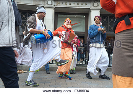Members of Hare Krishna dance and sing amongst passing pedestrians, on Oxford Street in central London, UK. - Stock Image