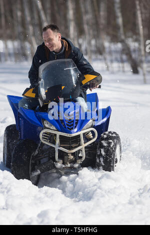 A man in warm jacket riding snowmobile in the winter forest - Stock Image