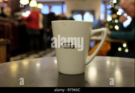 Cafe Nero coffee cup on a table inside shop store interior and blurred Christmas tree decorations in Cardiff Wales UK. KATHY DEWITT - Stock Image