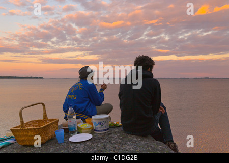 Two teenagers having an evening picnic by the sea in the 'Archipelago of Stockholm', Sweden. - Stock Image