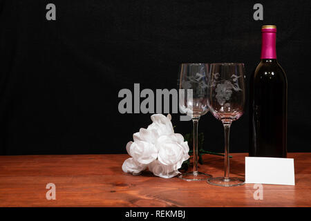 Beautiful etched wine glasses and bottle of red wine and white roses on wooden table with name tag on dark background. Valentines, Mothers Day, Easter - Stock Image