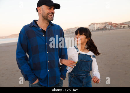 Funny father and daughter laughing while walking arm in arm on the beach at sunset - Stock Image