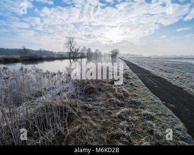 River Aller on a frozen winter day, hiking and cycling path along the river, between Celle and Altencelle, Germany - Stock Image