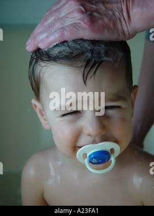 Hair wash of boy by mother in bath tube in private bathroom at home - child with pacifier (don't like washing - Stock Image