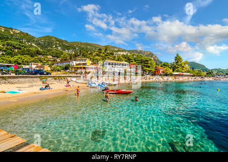Tourists relax in the clear turquoise waters and on the sandy Palaiokastritsa beach on the Aegean island of Corfu, Greece. - Stock Image