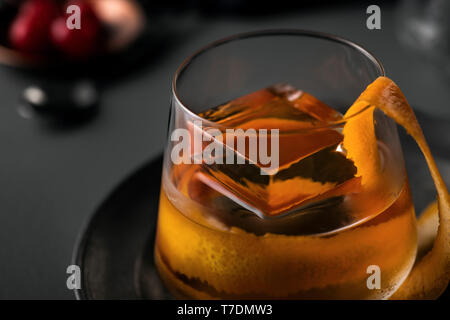 Old fashioned cocktail with large orange peel and artisan ice cube on a dark metal platter with cherry garnish. - Stock Image
